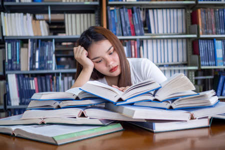 Asian female students are tired of reading in the library. A teenage female student sits on a table with a pile of books placed in front of them. Concept of reading books, boredom, test preparation