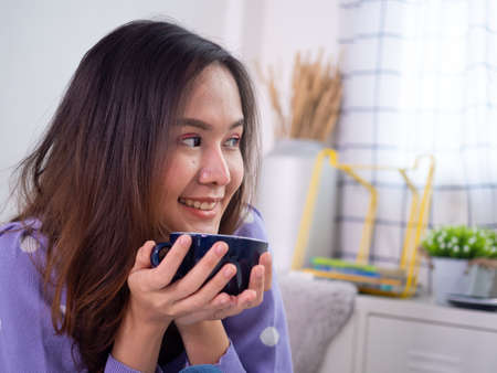 Young women are drinking coffee or hot tea in the bedroom after waking up in the morning. Women are enjoying and relaxing with free time in holiday.