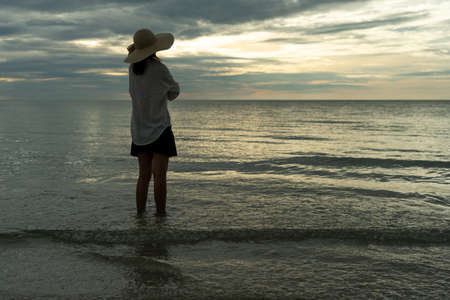A young woman wearing a hat stands alone on an empty sandy beach by the sea. Lonely young tourists look at the horizon. The concept of alone, travel