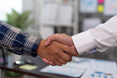 Business people shake hands to celebrate partnerships and business agreements. Effective communication and handshake concepts.
