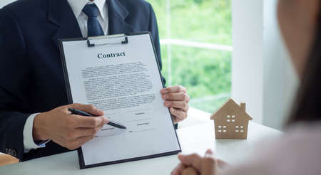 The hand of the sales department or the businessman points out the position to sign the contract. The sales manager explains the terms of a contract to buy or lease, mortgage land or real estate. Foto de archivo