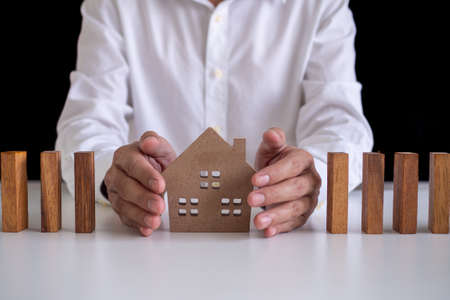 Male insurance agent is using a hand to protect the home. Home insurance or house insurance concept.
