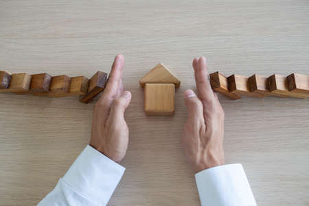 insurance with hands protect a house. Home insurance or house insurance concept Foto de archivo
