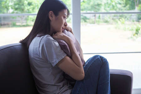 Asian good-looking women are sad and depressed. A woman sitting blankly on the sofa. A woman is disappointed, unhappy, or has problems with her boyfriend. Woman concept of depression