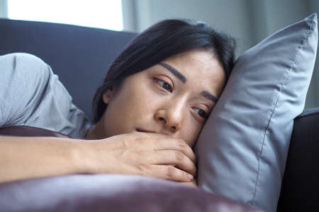 The girl hugged the pillow on the sofa inside the house sad and absent-minded feel bad about the things that happened.