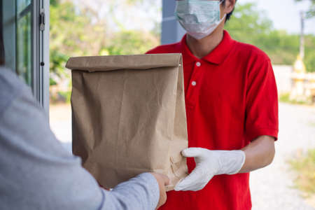 a courier wearing a red uniform with gloves and face masks to prevent the risk of contamination in delivering food to the hands of customers. food delivery sevices