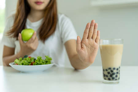 Healthy women do not eat pearl milk tea and choose apple and salad vegetables. Women reject foods and drinks but eat healthy vitamin food. Concept diet and good health. Foto de archivo