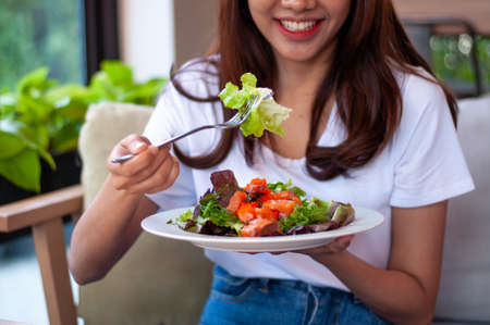 Beautiful Asian women are enjoying eating salad with salmon to lose weight. Healthy young woman eating vegetable salad. Dieting , Healthy food concepts.