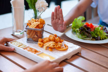 Young women reject fried foods and opt for a healthy salad. Women are losing weight by reducing fried foods, excess fat, dieting. good health, weight loss.