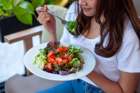 Young women intending to lose weight are eating a salmon vegetable salad for good health. Women choosing healthy food diet concept Foto de archivo