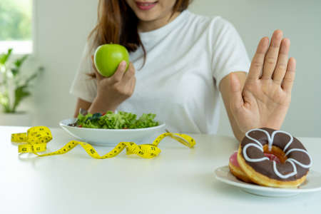 Women reject junk food or unhealthy foods such as doughnuts and choose healthy foods such as green apples and salads. Concept of fasting and good health. Foto de archivo