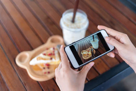 Women are using smartphones to focus on taking pictures of snacks and water in a coffee shop. Women take photo for social media updates or restaurant reviews. Foto de archivo