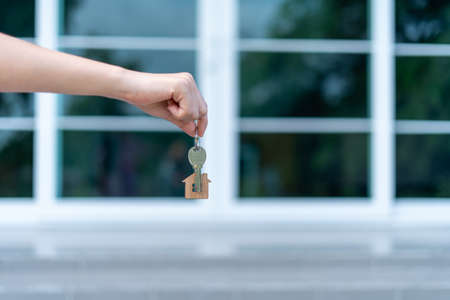 A woman's hand is handing over a key with a key ring house in the background of a modern house. Concept of home sales-lease, New house Foto de archivo