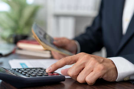 A male businessman is calculating the cost of economic profit and loss of business. Businessman presses a calculator with his finger to calculate office expenses.