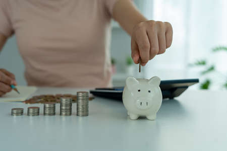 Woman's hand is putting coins in a piggy bank with piles of coins placed next to them to save money as expenses and investments. The concept of saving money, investment finance business