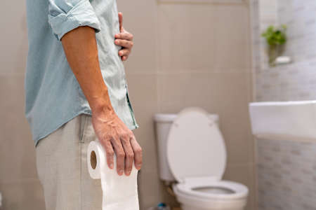 Man holding tissue paper roll standing in front of toilet. Men have abdominal, diarrhea or waist pain. Stomach health problem.