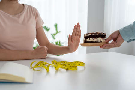 Skinny women refuse to eat chocolate cake. Women do not eat trans fats and sugar. diet concept
