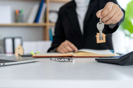 Home insurance broker or salesman holding a house key given to a new homeowner. Selling houses Real estate and property concept. Foto de archivo