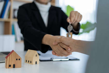 the sales representative shake hands and delivering the keys to the new homeowners after the purchase and sale agreement has been completed.