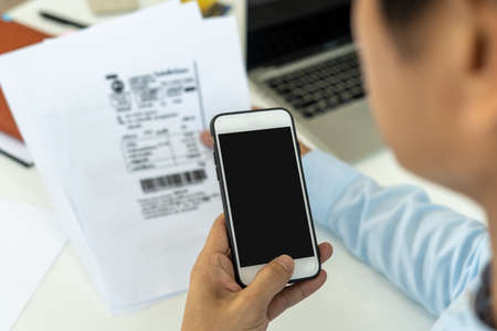 hand holding smart phone to scan QR code from invoice on papers for the bills. Scan, bar code online bill payment concept