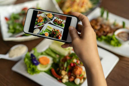 Woman take picture of a meal on the table after ordering food online to eat at home. Photography and use phone concepts Foto de archivo