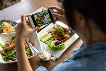 A woman's hand using a smartphone to photograph lunch or dinner in a restaurant. Women use their phones to take photos of food in trendy style for social media.