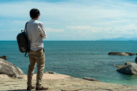 A young backpacker stands on the rocks by the sea, taking in a beautiful view. Traveling alone on vacation. Foto de archivo