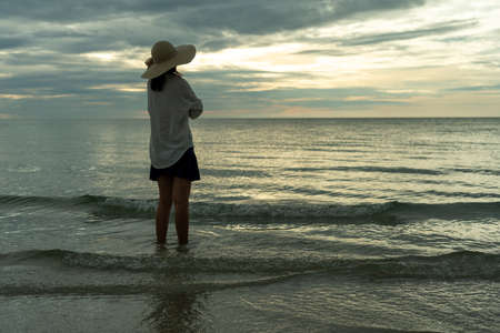 Woman wearing a hat walks alone on an empty sandy beach at sunset. A lonely and depressed young woman stands on the sand of the beach on holiday.