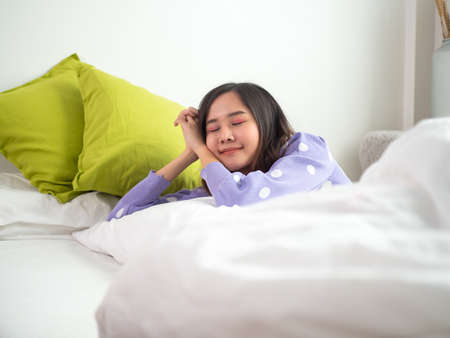 Asian young women enjoy soft bedding and mattresses in modern bedrooms. A teenage girl rests a good night's sleep on holiday in bed happily. Sleepy woman. Foto de archivo