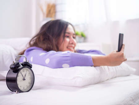 Woman wake up and use phone on bed. Young Asian women play games or chat happily in bed with an alarm clock showing the time.