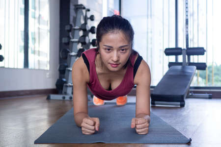 Asian women exercise planking on mats at the floor of the gym. Strong women are exercising  for good health. The concept of fitness women Foto de archivo