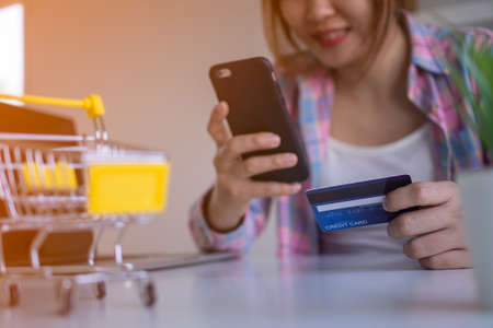 Happy young women use mobile phones and credit cards to payment online shopping. Women shop online through apps easily at home. Online shopping concept. Foto de archivo