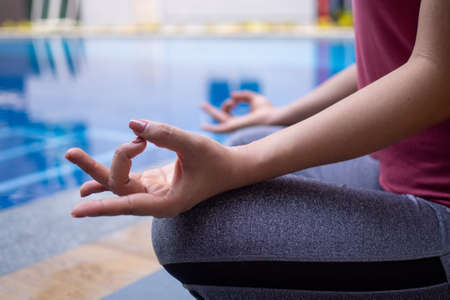 Women calmly meditate by the pool. Woman doing yoga pose practicing peace of mind. yoga concept