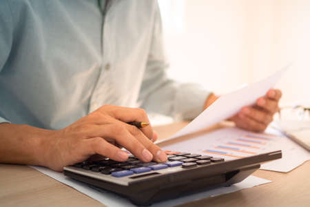 Business people sit at the desk using a calculator to calculate the profit-loss figures shown in the document graph. Concept of using calculator