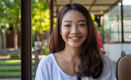 A beautiful young Asian woman feels happy, smiling and looking relaxed at the camera in a coffee shop. Smiling Asian girl