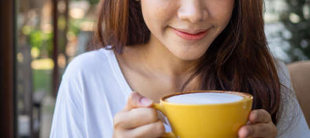 Young woman's face relaxing with hot milk or coffee during morning. Woman drink coffee in a cafe. good feeling with drink coffee concept Foto de archivo