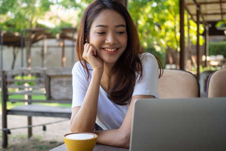 A smiling Asian blogger sits in cafe watching the camera record live video on personal computer. View of web cam video conferencing with online viewers. Website creator and product review