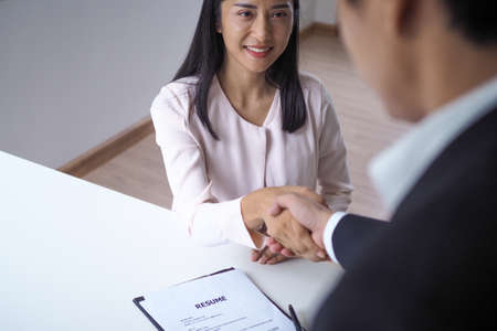 Asian female smiling and handshake with management after a successful job interview. Shaking hands in hiring or making a first impression.  interviewing ideas