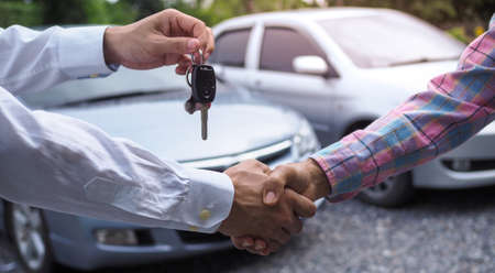 The salesperson held the key and handed it to the customer after the deal was successful. Ideas for renting a car or buying a car