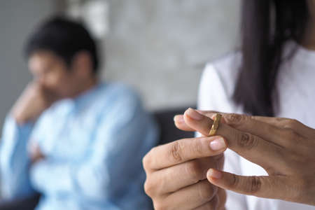 Sad woman's hand removing a wedding ring after an argument with husband. The concept of divorce, love problem