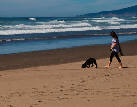 casualy: a girl casualy dressed walking her black dog on the beach.
