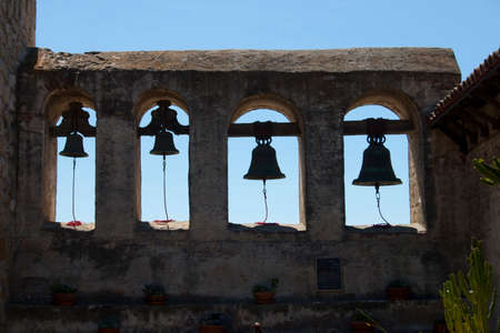 four mission bells at San Juan Capistrano, brick wall, blue sky photo