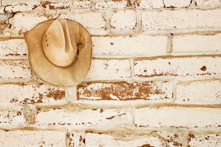 country western: a straw cowboy hat hanging on an brick adobe wall that was white washed with open space for text to the right of the hat.