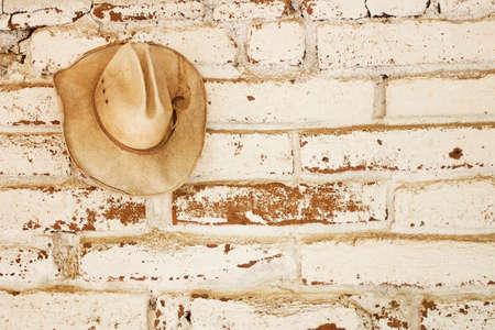 adobe wall: un cappello da cowboy di paglia appeso su un muro di mattoni di adobe che era bianco lavato con spazio aperto per il testo a destra del cappello.