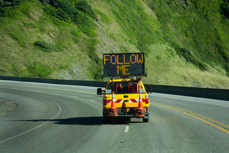 follow through: road construction ahead you must follow the pilot truck on a road through the mountains. lighted sign says follow me. Stock Photo