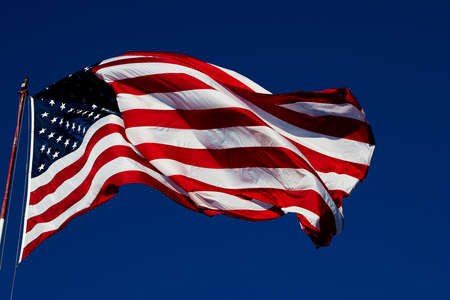 windy day: windy day clear blue skies with American flag blowing on a flag pole. Room for text