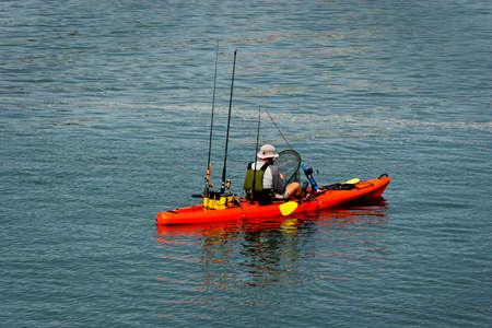 pull up: kayak arancione, pagaie giallo, con canne da pesca nella parte posteriore. L'uomo con la schiena alla telecamera in possesso di una rete sempre pronto a tirare su un pesce.