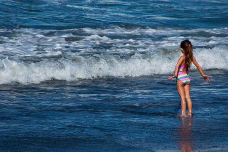chica surf: una joven blanca con pelo rubio que llevaba un traje de ba�o del arco iris, que juega en la resaca de la muchacha