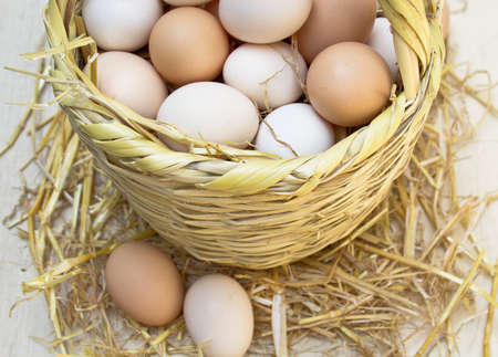 Fresh raw eggs in straw basket.