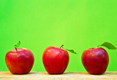 Red apples on wooden table.